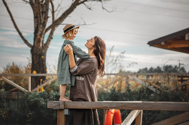 Beautiful happy family mother and daughter together portrait on a wooden pier