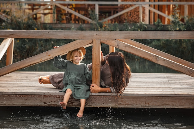 Beautiful happy family mother and daughter together on a wooden pier on the lake shore