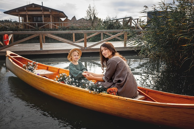 Beautiful happy family mother and daughter in a wooden boat  on the lake together