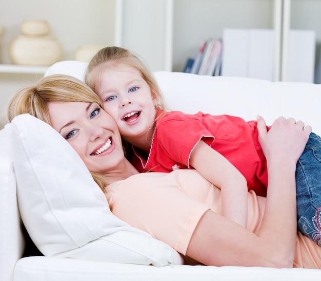 Красивая счастливая семья молодой блондинки матери и ее маленькой красивой дочери - в помещении