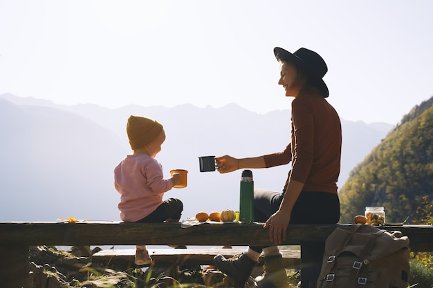 Beautiful happy family outdoors mother and daughter on a picnic in mountains