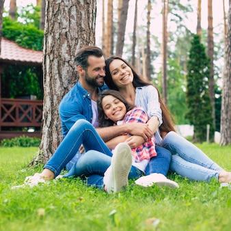 Красивая счастливая семья, сидя вместе на траве