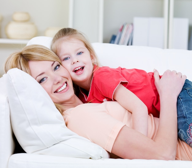 Beautiful happy family of young blond mother and her little pretty daughter - indoors
