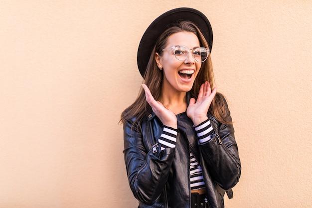 明るい黄色の壁に分離された革のジャケットと黒い帽子の美しい幸せなファッションの女の子