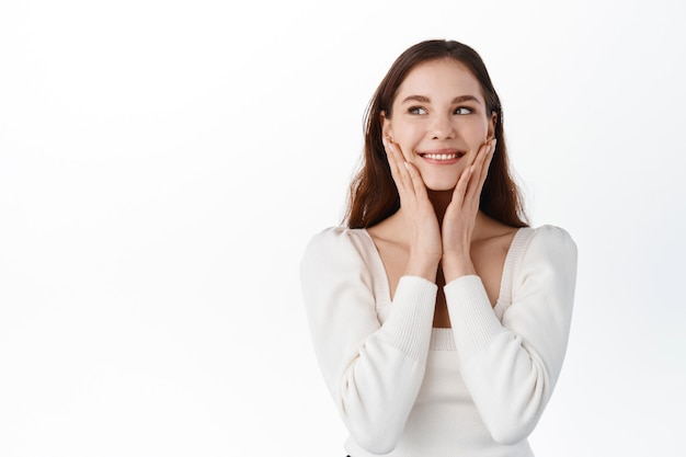 Beautiful happy female model with natural nude make-up, smiling from compliments, blushing and looking aside, touching face cheeks and rejoicing, being praised, standing against white wall