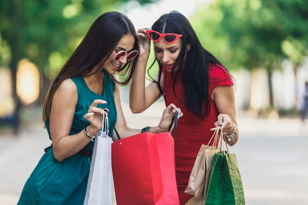 Beautiful happy females in sun glasses looking into shopping bags walking at the street.
