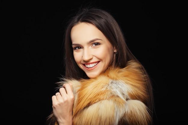 Beautiful happy girl in fur coat