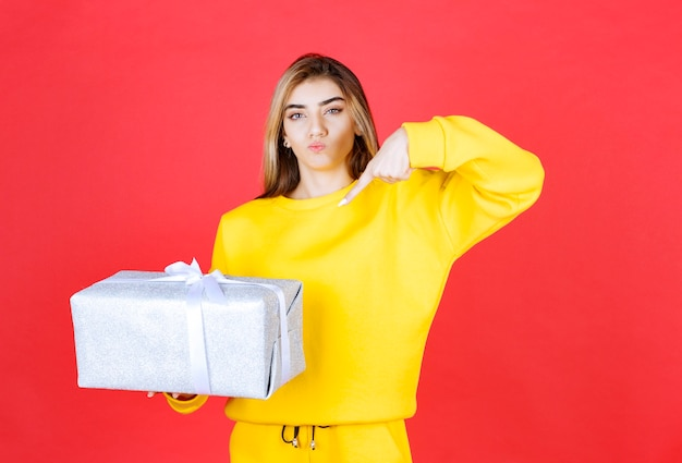 Beautiful happy girl holding gift box on red wall