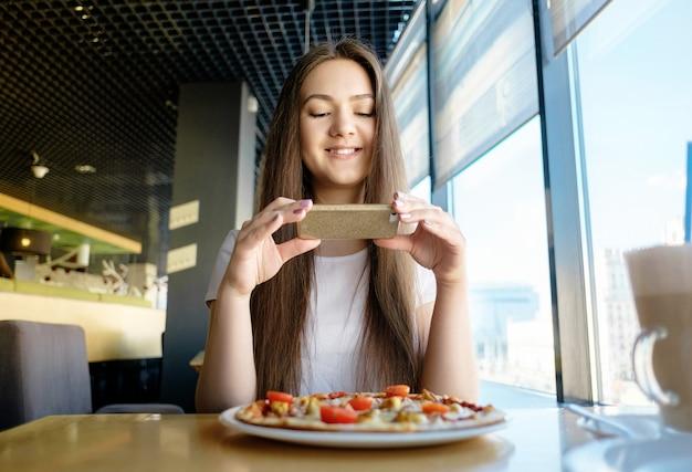 Красивая счастливая девушка делает фото еды в кафе, латте на столе пиццы