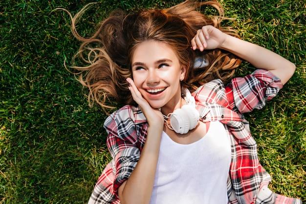 草の上に横たわって美しい幸せな女の子。良い春の日を楽しんでいるヘッドフォンでうれしそうな若い女性。
