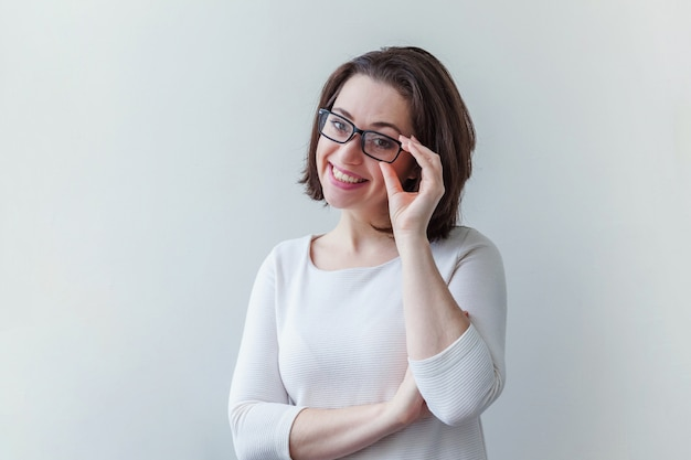 Beautiful happy girl smiling. beauty simple portrait young smiling brunette woman in eyeglasses isolated on white
