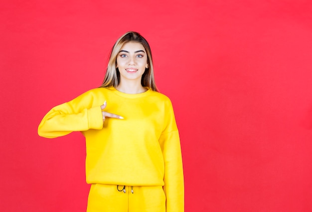 Beautiful happy girl standing and pointing something on red wall