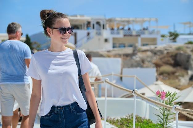 그리스 산토리니 섬에 있는 아름다운 행복한 소녀 관광, 지중해를 여행하는 10대 여성. 흰색으로 유명한 섬 건축과 푸른 하늘 배경, 복사 공간