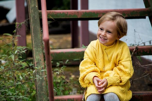 黄色のニットセーターで短い散髪の美しい幸せな女の子が階段に座っています
