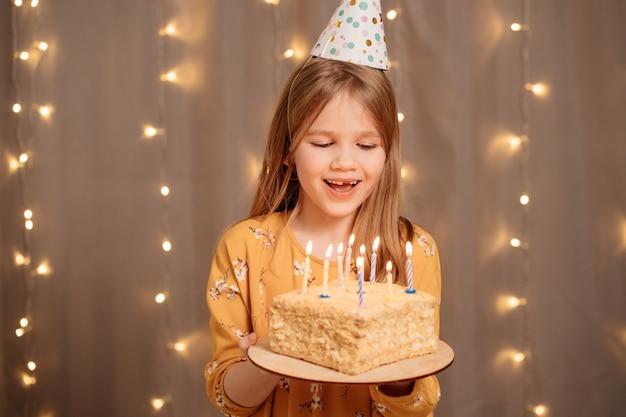 バースデーケーキと美しい幸せな女の子。パーティーで願い事をして火を消す伝統
