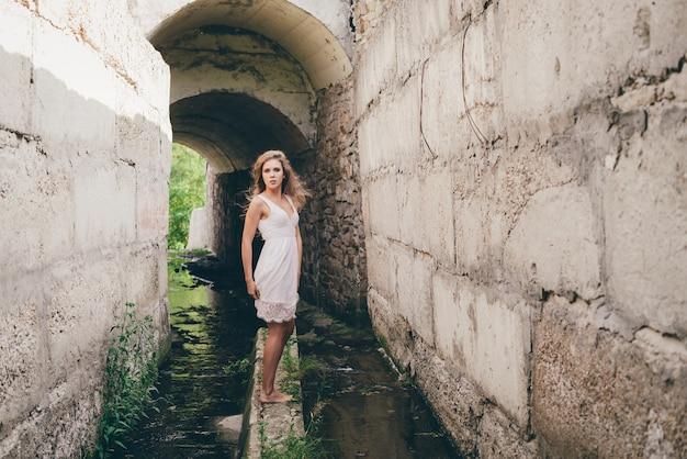 흰 드레스에 곱슬 자연 머리를 가진 아름 다운 행복 소녀 터널에서 춤을