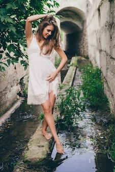 녹색 나무 잎 근처 흰색 드레스에 곱슬 자연 머리를 가진 아름 다운 행복 한 소녀. 여름 아름다움 초상화.
