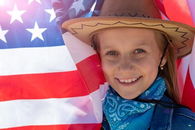 Красивая счастливая девушка с зелеными глазами на фоне американского флага в яркий солнечный день.