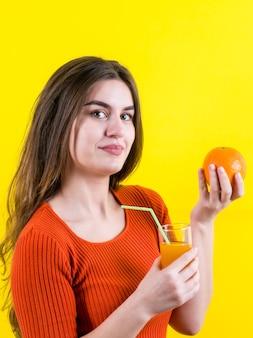 黄色のオレンジとオレンジジュースと黄色の美しい幸せな女の子