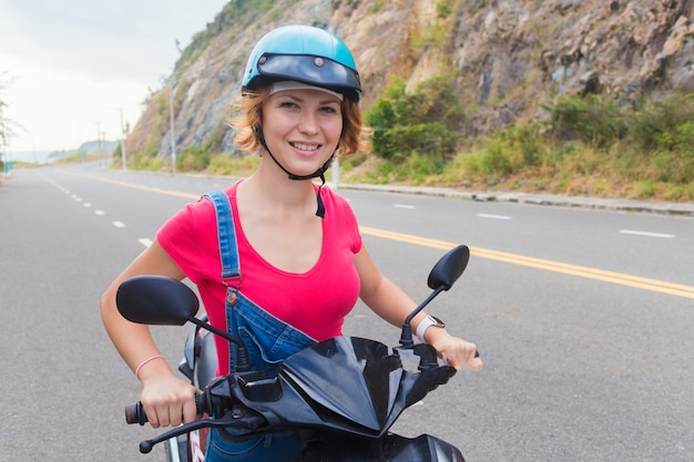 Beautiful happy girl, young woman, biker or motorcyclist is driving motorcycle, moped or bike, , smiling. female rider in helmet for safety riding on road in mountains in summer day.