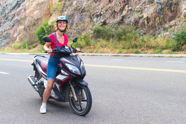 Beautiful happy girl, young woman, biker or motorcyclist  is riding, driving motorcycle, moped or bike, , smiling. female rider  in helmet on the road in mountains in a summer day.