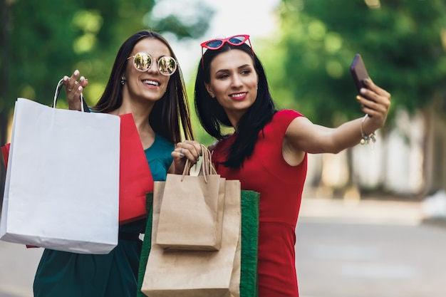 Beautiful happy girls in sun glasses holding shopping bags, making selfie on smart phone and smiling