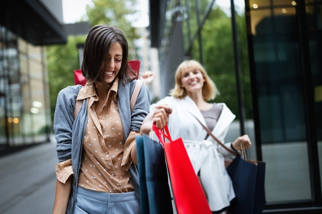 Красивые счастливые девушки с хозяйственными сумками гуляют по улице в торговом центре