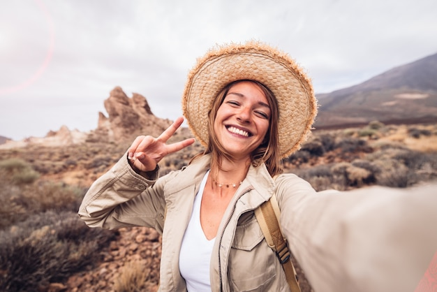 Красивая счастливая женщина hiker принимая selfie поход в гору на каникулы.