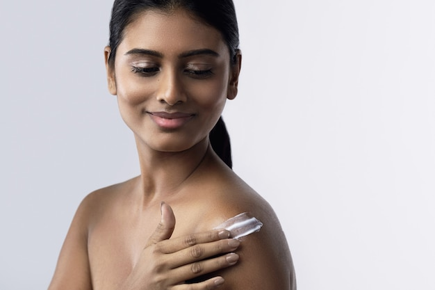 Beautiful and happy indian woman applying moisturizing cream or sunblock lotion on her body