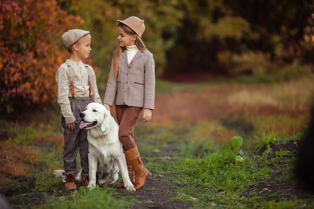 美しい幸せな子供たちの兄と妹は彼らのペットの犬のレトリーバーを歩いています