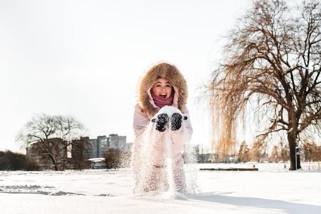 冬の帽子、雪片で覆われたスカーフを身に着けている美しい幸せな笑いの少女。アクティブなライフスタイル。冬の森の風景の背景。