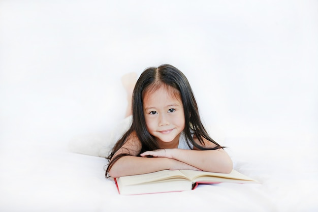 Beautiful happy little asian kid girl reading hardcover book lying on bed against white background.