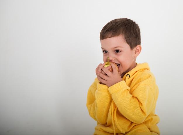 Красивый счастливый маленький мальчик в желтом костюме на белом баккара