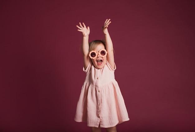 Красивая счастливая маленькая девочка в розовом платье в очках