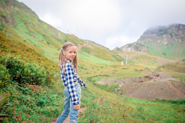Beautiful happy little girl in mountains in the background of fog