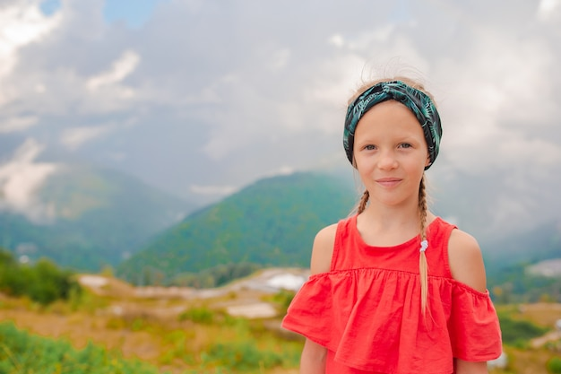 Beautiful happy little girl in mountains