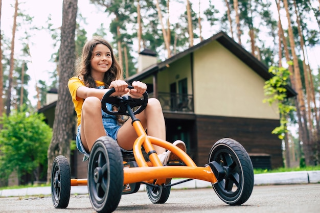 A beautiful happy little girl on vacation is riding on a bike and have fun in the summer forest camp