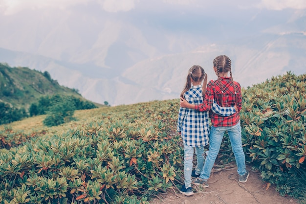 Beautiful happy little girls in mountains in the background of fog