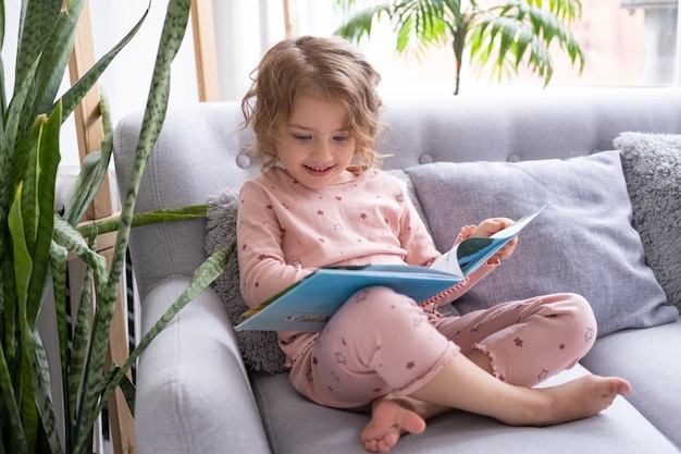 Beautiful happy little kid caucasian girl in pajama reading book sitting on couch at home.