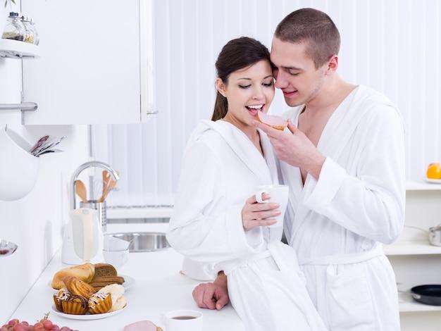 キッチンで朝食をとっている美しい幸せな愛情のあるカップル