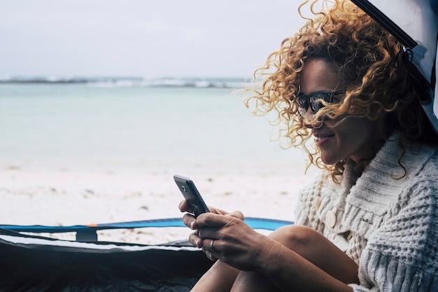 Красивая счастливая кавказская женщина среднего возраста улыбается и наслаждается кемпингом на пляже возле океанских волн. используйте телефон для подключения к интернету и обмена текстовыми сообщениями с друзьями дома.