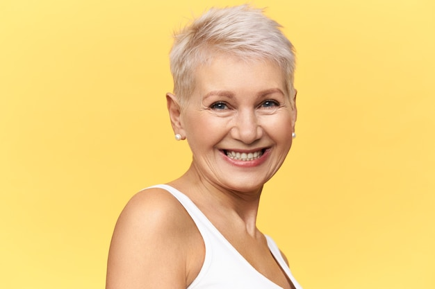 Beautiful happy middle aged woman with short dyed hair looking at camera with cheerful broad smile, laughing at funny joke.