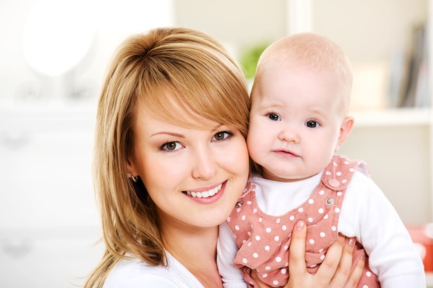Красивая счастливая мать держит на руках новорожденного ребенка - в помещении