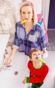 Beautiful happy mother and little son in bathrom brushing teeth together