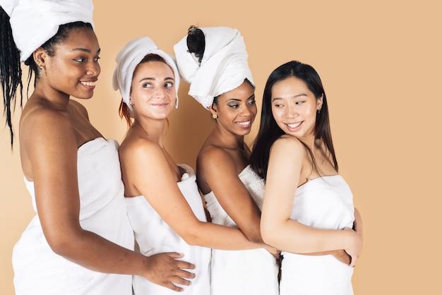 Beautiful happy multiethnic women wear white bathrobes on head skincare spa relaxation