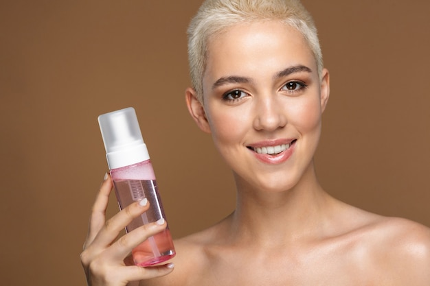 A beautiful happy optimistic smiling young blonde stylish woman with short haircut posing isolated over dark beige wall wall holding bottle with cosmetics water.