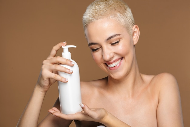 A beautiful happy optimistic smiling young blonde stylish woman with short haircut posing isolated over dark beige wall wall holding bottle with cream lotion.
