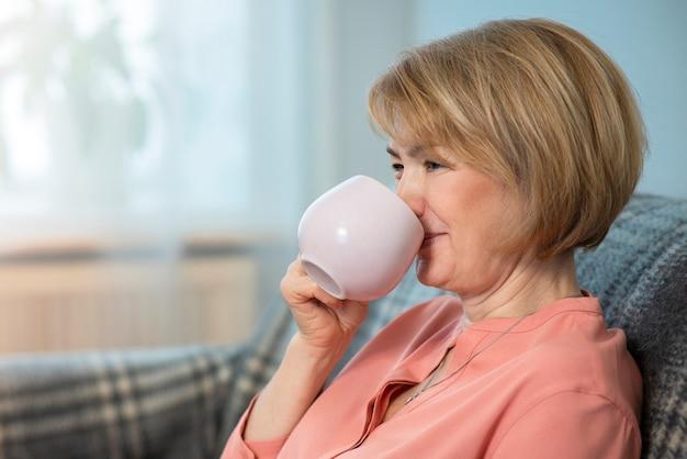 Красивая счастливая позитивная жизнерадостная женщина, взрослая пожилая старшая дама пьет чай или кофе из