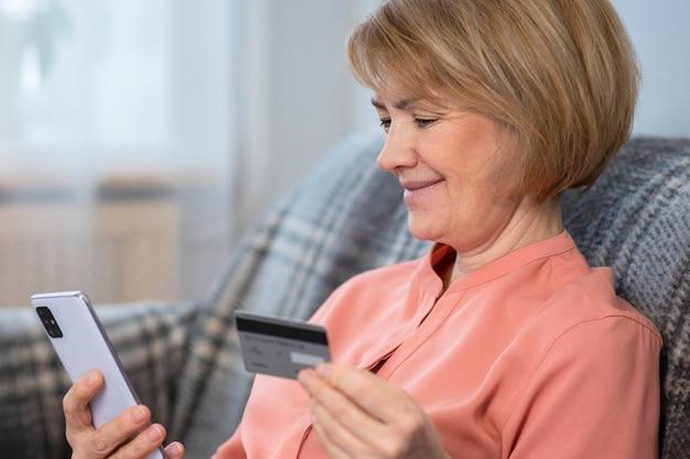 Красивая счастливая положительная пожилая старшая женщина дома с мобильным телефоном, смартфоном, покупкой, использованием