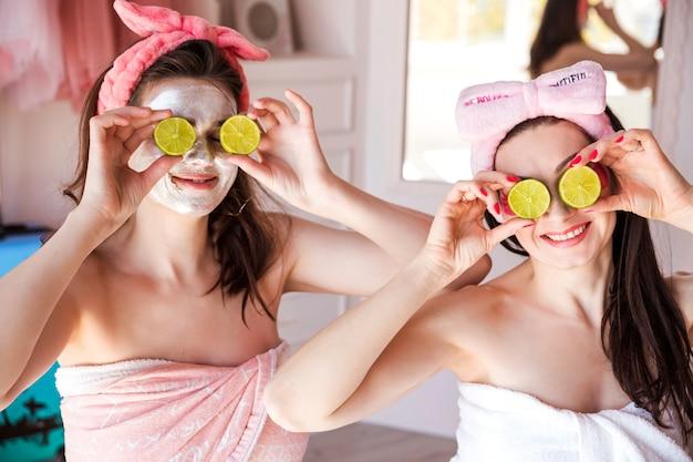 Красивые, счастливые, позитивные женщины, завернутые в полотенце, с косметической повязкой на голове и с лаймами на глазах. девушки улыбаются и смотрят в камеру. Premium Фотографии